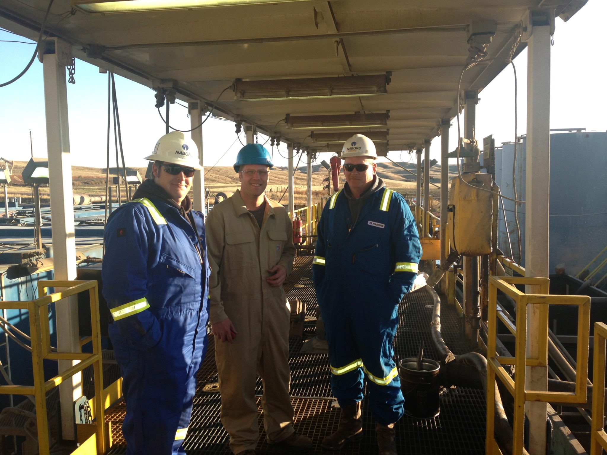 Agassiz Chemical's Steve Hareland (middle) poses with Nabor's Tyson Olsen (left), rig manager, and Greg Burquist (right), drill superintendent, on a Nabor's well pad